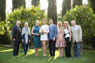 bride-in-a-mini-mod-dress-groom-in-blue-blazer-black-pants-with-guests-in-san-ysidro-ranch-garden