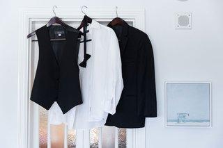 wedding-attire-for-groom-on-hangers-in-grooms-suite-casa-del-bar-black-tuxedo-vest-bow-tie-shirt