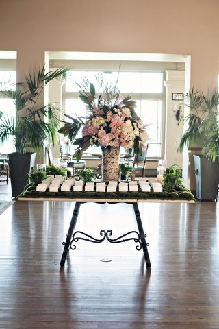 wedding-escort-cards-on-table-covered-in-moss-flower-arrangement-in-birch-tree-trunk