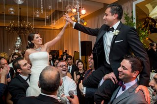 bride-groom-lifted-by-guests-holding-hands-lively-reception-wedding-fun-dancing
