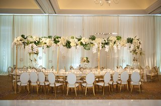 serpentine-table-white-gold-chairs-tall-centerpiece-design-of-white-orchids-roses-monstera-leaves