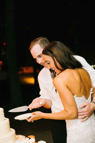 bride-in-a-strapless-alencon-lace-dress-groom-in-white-shirt-cut-white-wedding-cake-from-susiecake