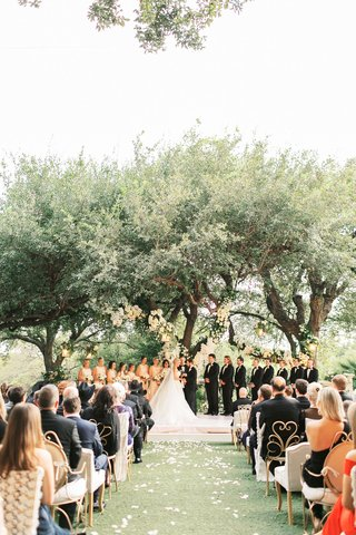 wedding ceremony garden grass lawn tree decorated with flowers raised stage gold lace guest seating