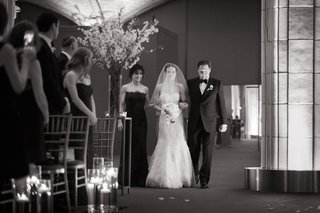 black-and-white-photo-of-a-bride-walking-down-the-aisle-lead-by-her-parents