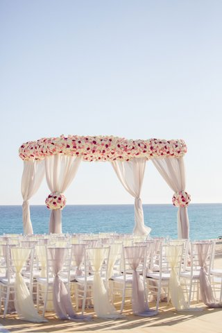 wedding-arbor-on-the-beach-destination-wedding-white-rose-pink-rose-fabric-on-back-of-chairs