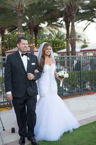bride-in-strapless-wedding-dress-hair-down-with-brother-escort-outdoor-wedding-ceremony-tuxedo