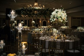 wedding-reception-with-round-and-rectangular-tables-white-flowers-greenery-candles-winter-decor-idea