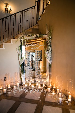 seating-chart-on-mirror-with-flower-embellishments-and-display-of-candles