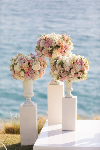 three-white-pillars-with-vases-full-of-white-and-pink-flowers-at-wedding-ceremony