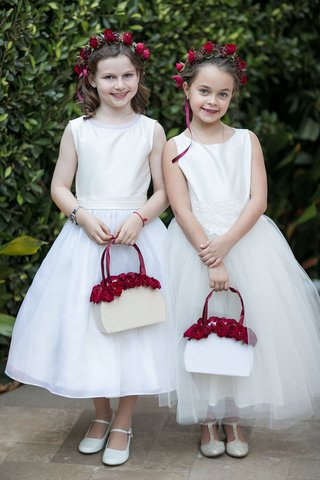 two-flower-girls-in-white-dresses-tulle-skirts-with-white-purse-baskets-red-flowers-flower-crowns