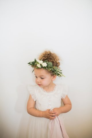 adorable-flower-girl-in-frilly-dress-with-flower-crown-with-lots-of-greenery