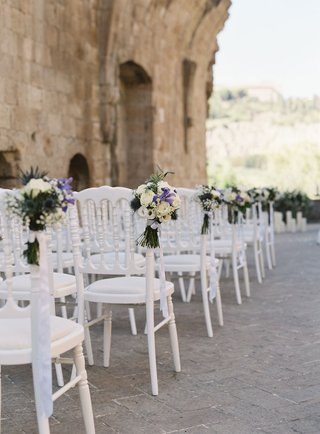 wedding-ceremony-in-italy-stone-ruins-white-chairs-greenery-white-purple-flowers-along-aisle