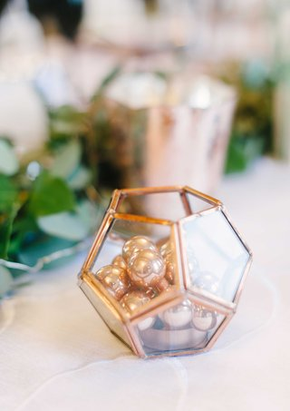 a-small-copper-geometric-terrarium-item-filled-with-small-beads-on-a-reception-table