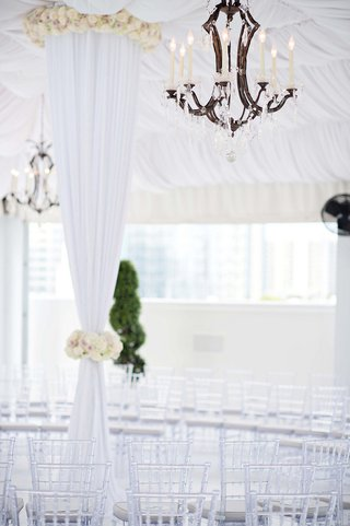 faux-candlelit-light-fixture-above-clear-chairs