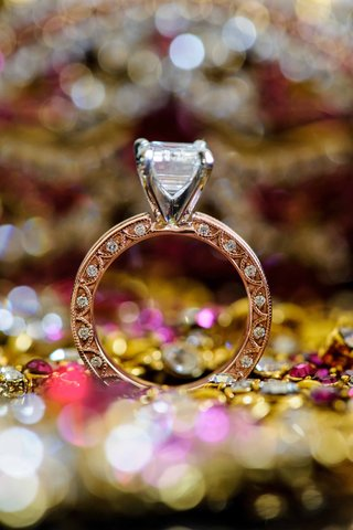 opulent-engagement-ring-with-large-diamond-and-detailed-band-standing-up-around-sparkling-colors