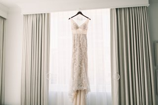 sleeveless-v-neck-lace-gown-with-nude-lining-hanging-in-the-window