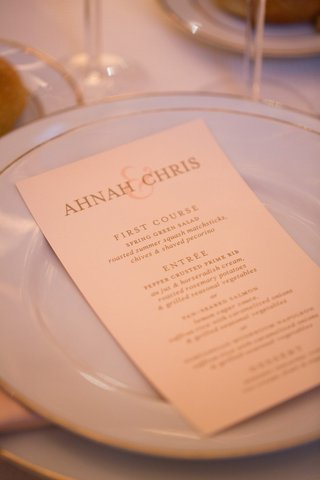 wedding-reception-menu-with-golden-and-pink-font-on-white-china-with-gold-rims