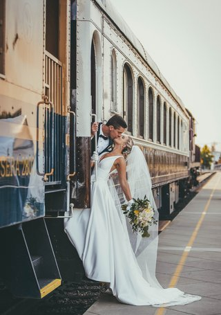 bride-in-stella-york-wedding-dress-kissing-groom-as-they-lean-out-of-a-train