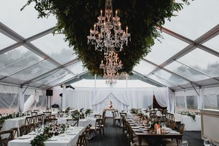 wedding-reception-greenery-chandelier-long-table-wood-low-centerpiece-white-drapery-kings-tables