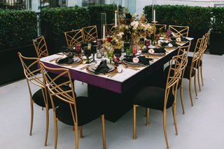 black-velvet-and-gold-back-chairs-around-white-marble-table-with-fall-hued-centerpiece-candlesticks