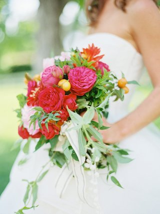 bride-holding-bright-wedding-bouquet-with-greenery-red-flowers-pink-flowers-and-fruit