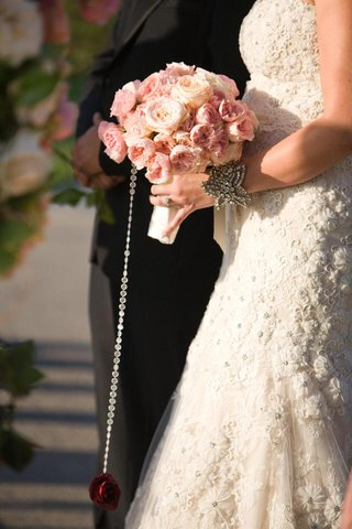 bride-walking-down-aisle-with-red-rose-hanging-from-bouquet