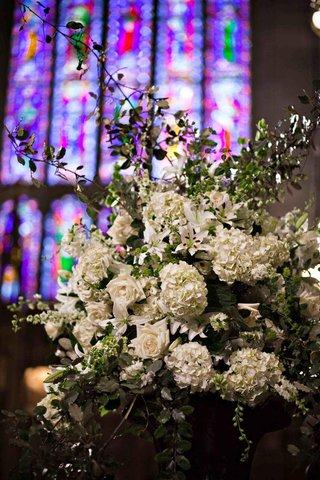 white-rose-and-hydrangea-arrangement-in-front-of-stained-glass-window