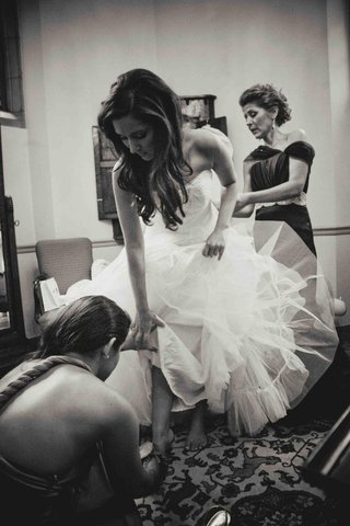 black-and-white-photo-of-bride-getting-dressed-with-mom-and-bridesmaid