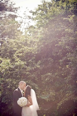 bride-and-groom-kiss-in-front-of-tall-hedge-in-nc