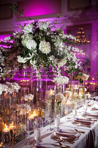 hurricane-vases-with-candles-and-white-flowers-at-reception