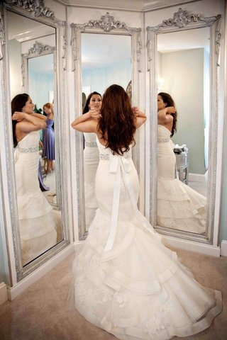 bride-in-three-way-mirror-with-ivory-tiered-wedding-dress