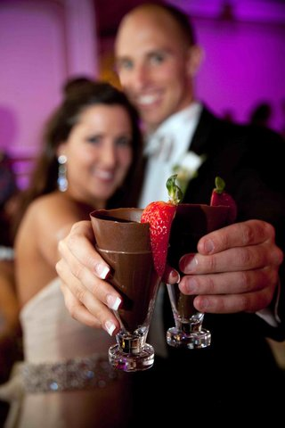 bride-and-groom-holding-shot-glass-with-chocolate-and-strawberry