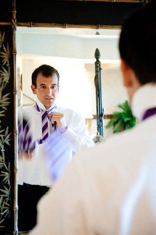man-tying-purple-striped-tie-in-mirror