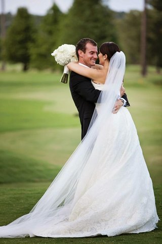 groom-picking-up-bride-in-lace-wedding-dress