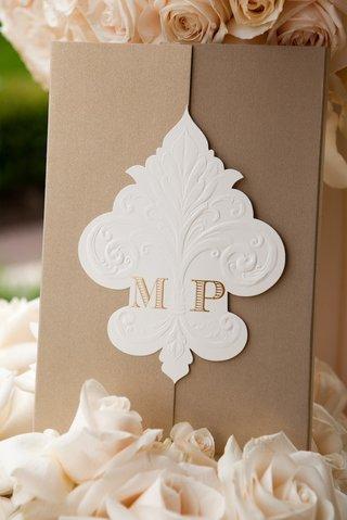 wedding-invite-with-monogram-on-fleur-de-lys-fastener