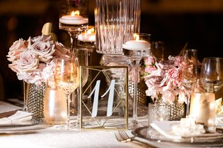 wedding reception gold vase pink lavender flowers roses floating candles gold frame white number calligraphy