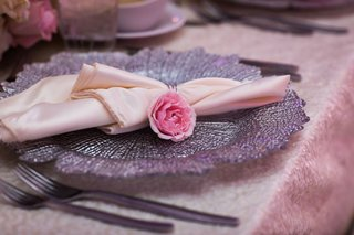 wedding reception silver charger plate with  napkin and single pink flower rose on top