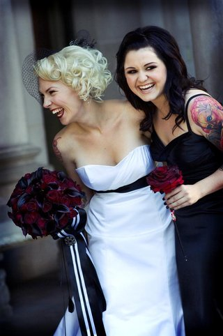 bride-in-a-strapless-alvina-valenta-gown-and-black-sash-with-bridesmaid-in-a-black-dress
