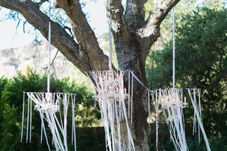 outdoor-wedding-ceremony-with-crystal-chandeliers-and-white-ribbons-hung-from-a-tree-at-altar