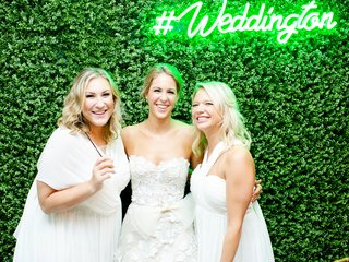 bride in mira zwillinger wedding dress with bridesmaids in white hedge wall photo booth backdrop neon sign green