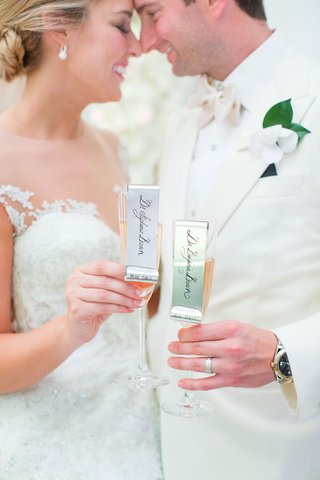 bride-and-groom-touch-noses-foreheads-while-holding-rose-champagne-with-metal-name-tags-escort-cards