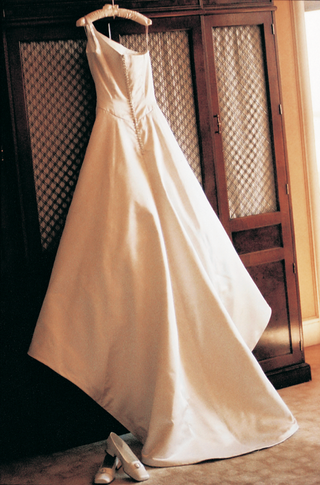 back-of-one-shouldered-wedding-gown-hangs-in-boudoir