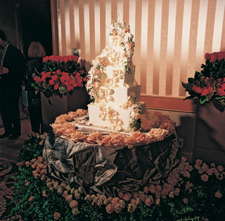 five-tier-cake-with-flowers-on-table-covered-with-roses