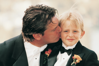 groom-kisses-young-ring-bearer-son-on-cheek