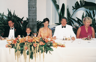 five-wedding-guests-at-long-table-with-tropical-floral-arrangement