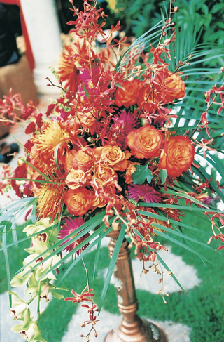golden-candlestick-holds-vibrant-tropical-floral-arrangement