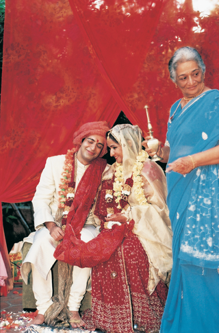 bride-and-groom-smile-on-mandap-structure