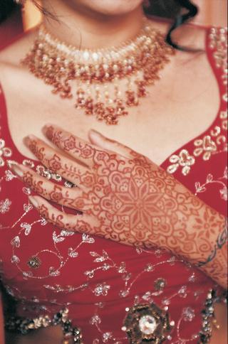 henna-tattoo-art-on-brides-hand-over-bodice