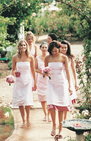bridesmaids-in-pink-dresses-walk-through-rose-garden
