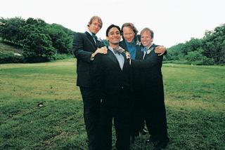 groomsmen-pose-outside-on-grassy-lawn